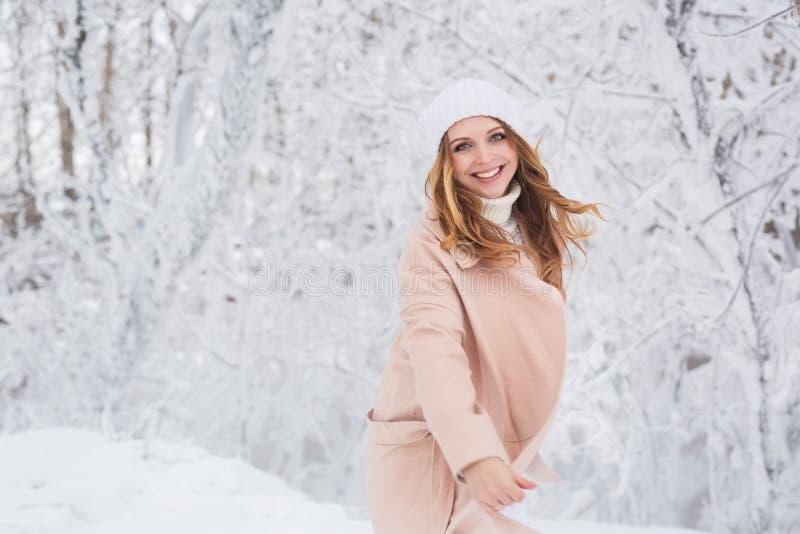 Retrato de la mujer bonita joven sonriente en una chaqueta beige en un bosque del invierno fotos de archivo