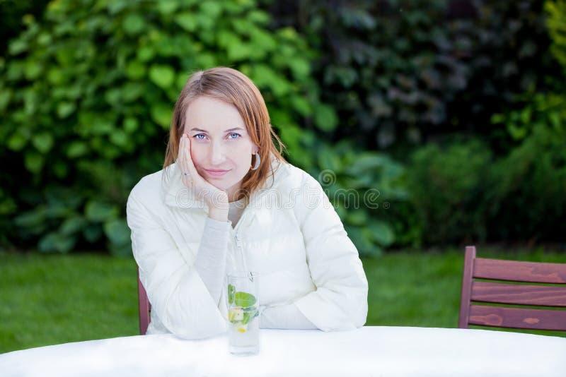 Retrato de la mujer bonita joven sonriente que se sienta en la tabla en Garde imágenes de archivo libres de regalías