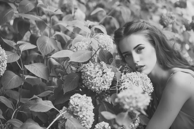 Retrato de la mujer bonita y de flores azules imagen de archivo