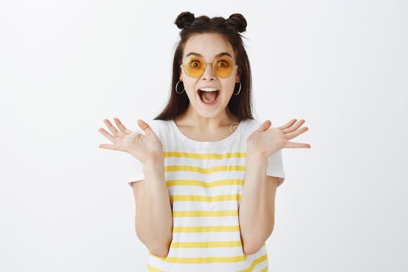 Retrato de la mujer brillante y elegante sorprendida e impresionada en gafas de sol y camiseta rayada amarilla, gritando y fotos de archivo