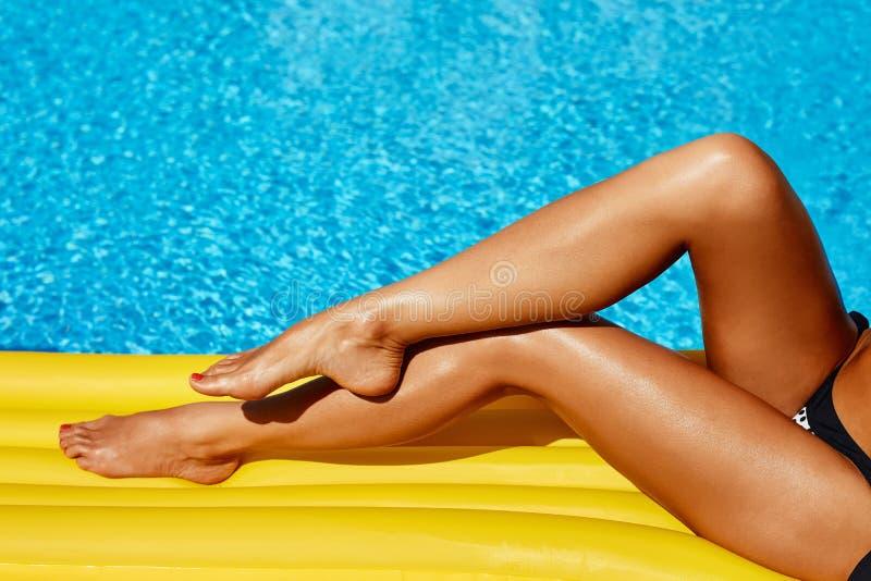 Retrato de la mujer bronceada hermosa que se relaja en bikini y sombrero en piscina Manicura roja polaca del gel D?a de verano y  imagen de archivo libre de regalías