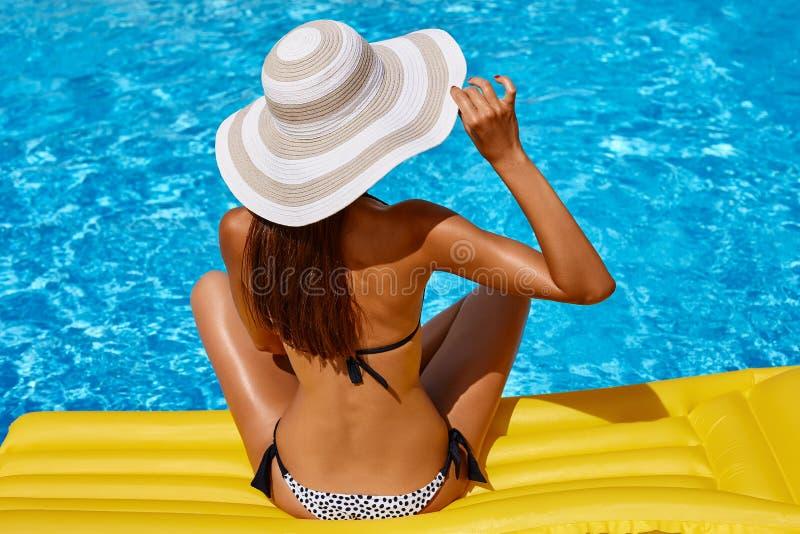 Retrato de la mujer bronceada hermosa que se relaja en bikini y sombrero en piscina Manicura roja polaca del gel D?a de verano y  fotos de archivo
