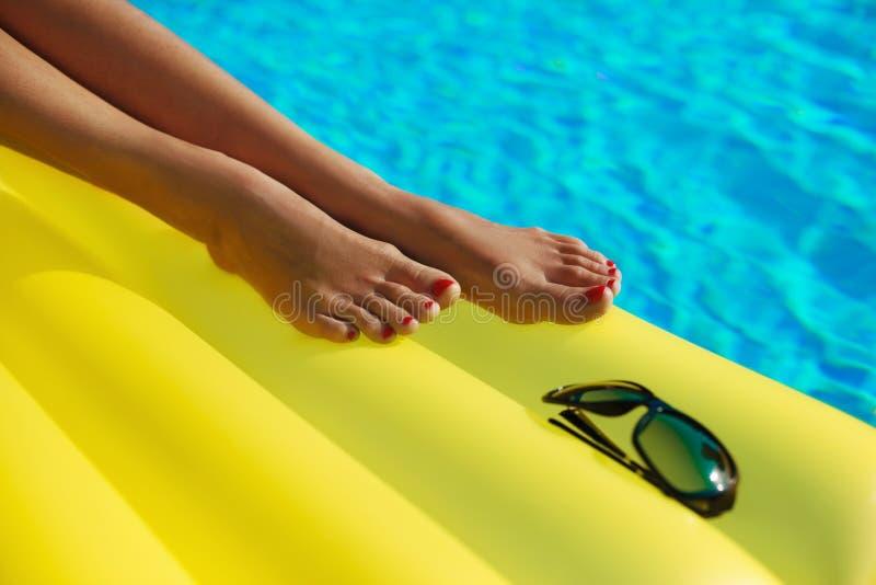 Retrato de la mujer bronceada hermosa que se relaja en piscina Gafas de sol y matress inflables Las piernas se cierran para arrib fotografía de archivo libre de regalías