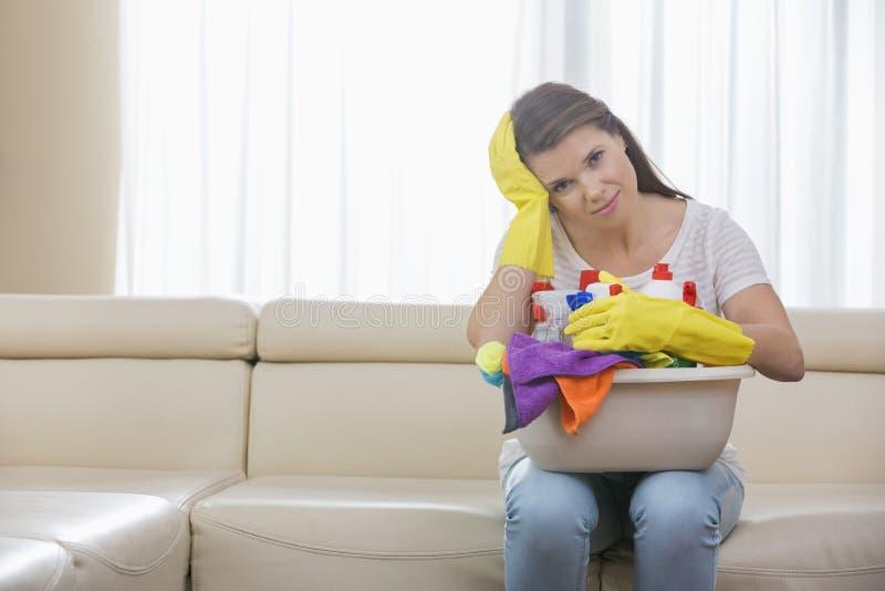 Retrato de la mujer cansada con la cesta de fuentes de limpieza que se sientan en el sofá en casa foto de archivo