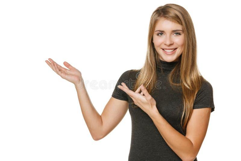 Mujer feliz que muestra el espacio de la copia fotografía de archivo