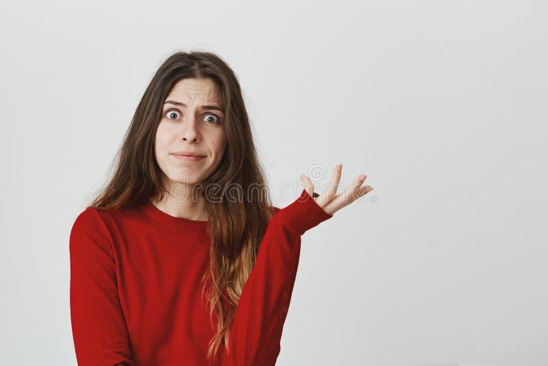 Retrato de la mujer caucásica atractiva en el top rojo que mira con los ojos hechos estallar que muestran tan qué gesto sobre el  foto de archivo
