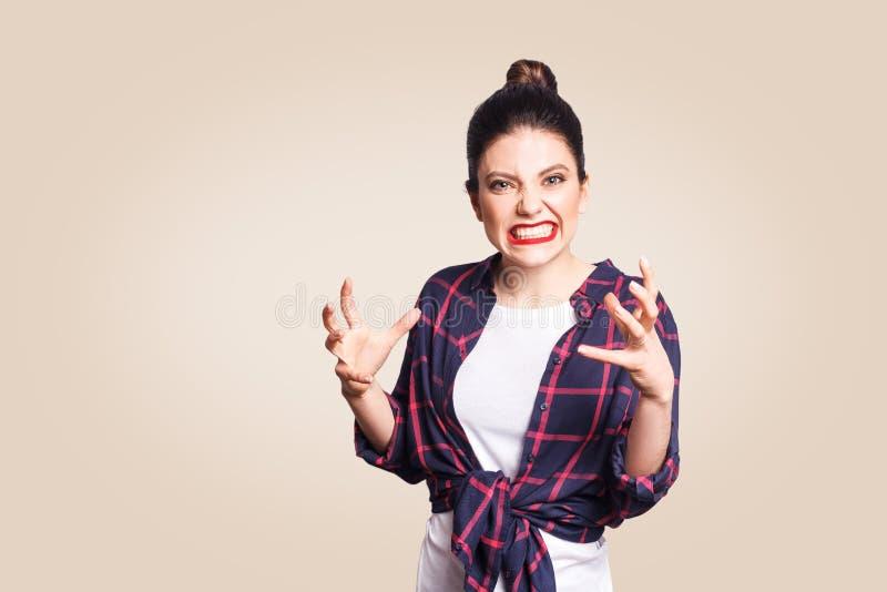 Retrato de la mujer caucásica diseñada casual joven subrayada y enfadada con el bollo del pelo que lleva a cabo las manos en gest foto de archivo libre de regalías