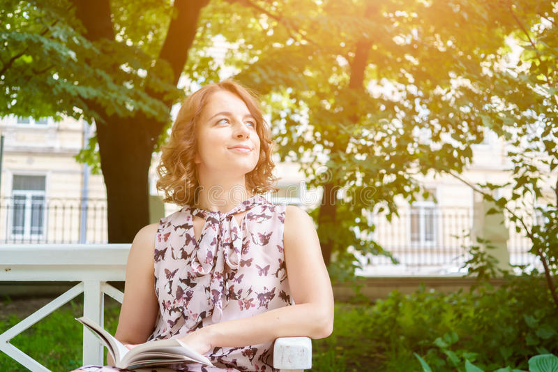 Retrato de la mujer caucásica en vestido del verano en banco de parque fotos de archivo libres de regalías