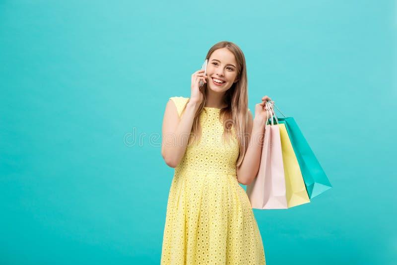 Retrato de la mujer caucásica de la moda feliz con los panieres que invita al teléfono móvil Aislado en fondo azul fotos de archivo