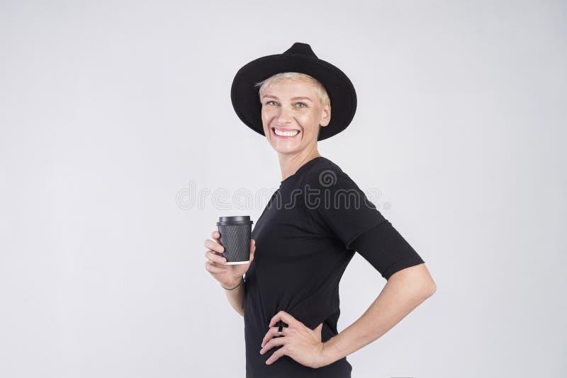 Retrato de la mujer caucásica rubia que lleva la ropa negra y el sombrero que comen la taza de café de papel disponible, presenta foto de archivo