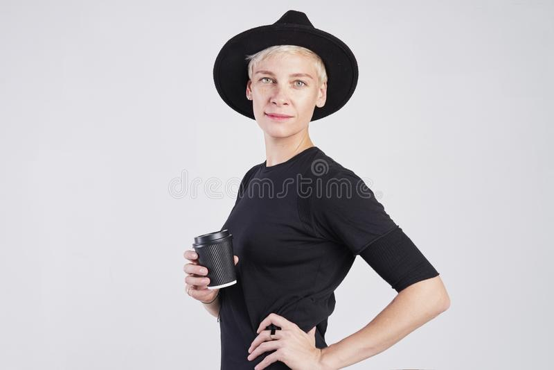 Retrato de la mujer caucásica rubia que lleva la ropa negra y el sombrero que comen la taza de café de papel disponible, presenta imágenes de archivo libres de regalías