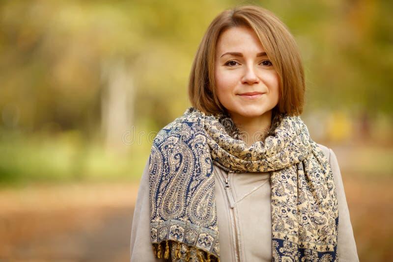 Retrato de la mujer caucásica sonriente elegante en fondo natural borroso imagen de archivo libre de regalías