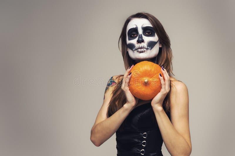 Retrato de la mujer con el maquillaje esquelético de Halloween que sostiene la calabaza sobre fondo gris imagenes de archivo