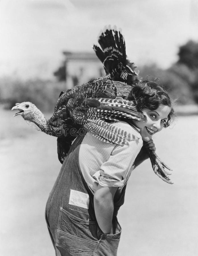 Retrato de la mujer con el pavo vivo lanzado con una honda sobre hombro (todas las personas representadas no están viviendo más d imagen de archivo libre de regalías