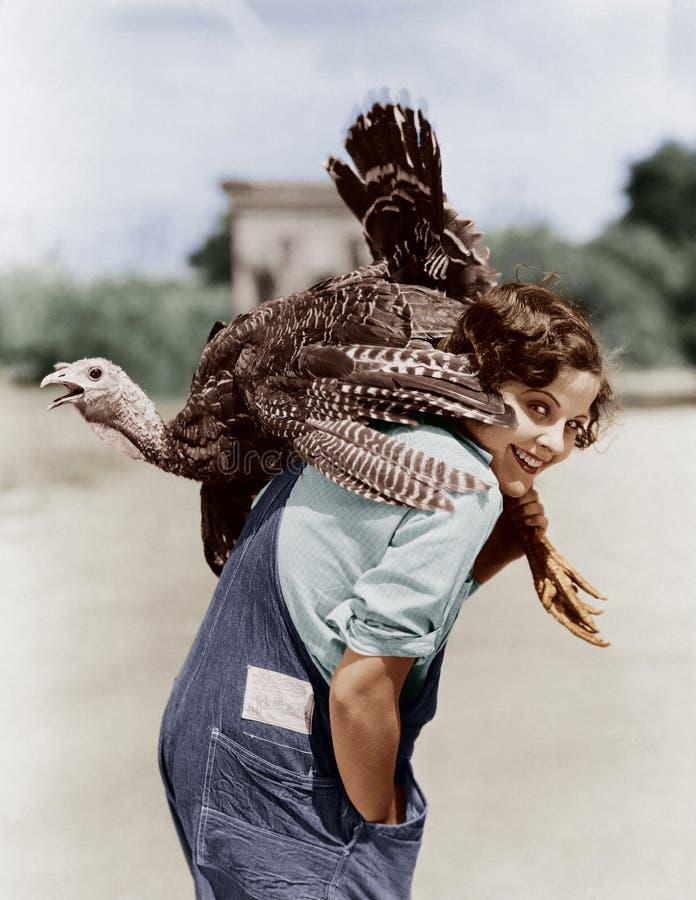 Retrato de la mujer con el pavo vivo lanzado con una honda sobre hombro (todas las personas representadas no están viviendo más d fotografía de archivo libre de regalías