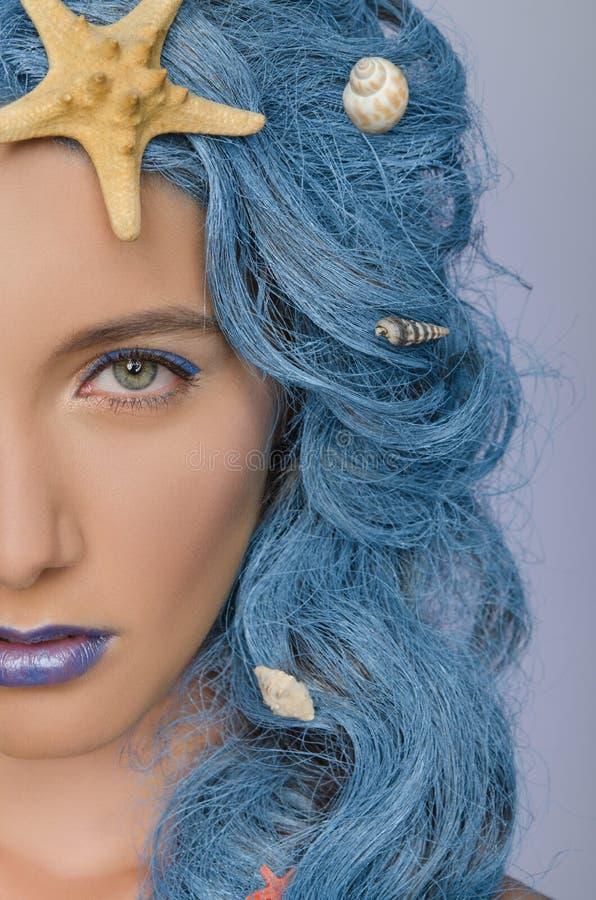Retrato de la mujer con el pelo y las cáscaras azules fotografía de archivo