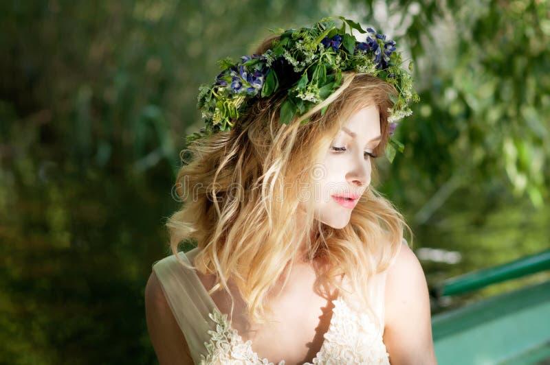 Retrato de la mujer con la guirnalda que se sienta en barco con las flores Verano fotografía de archivo libre de regalías