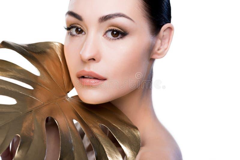 Retrato de la mujer con la hoja de oro grande cerca de la cara que mira la cámara imágenes de archivo libres de regalías