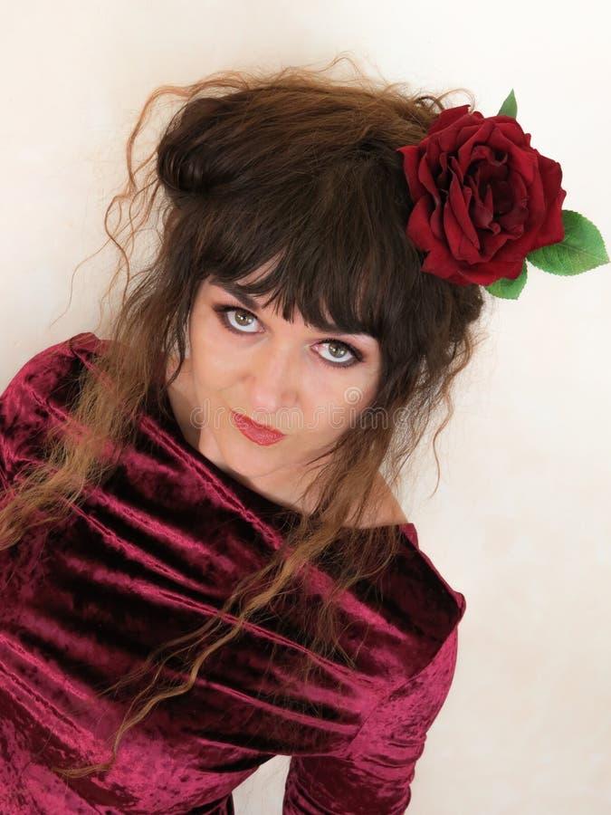 Retrato de la mujer con la rosa roja en pelo imagen de archivo