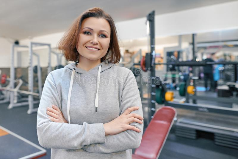 Retrato de la mujer confiada de mediana edad sonriente con las manos dobladas en el gimnasio fotografía de archivo libre de regalías