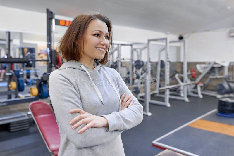 Retrato de la mujer confiada de mediana edad sonriente con las manos dobladas en el gimnasio fotos de archivo