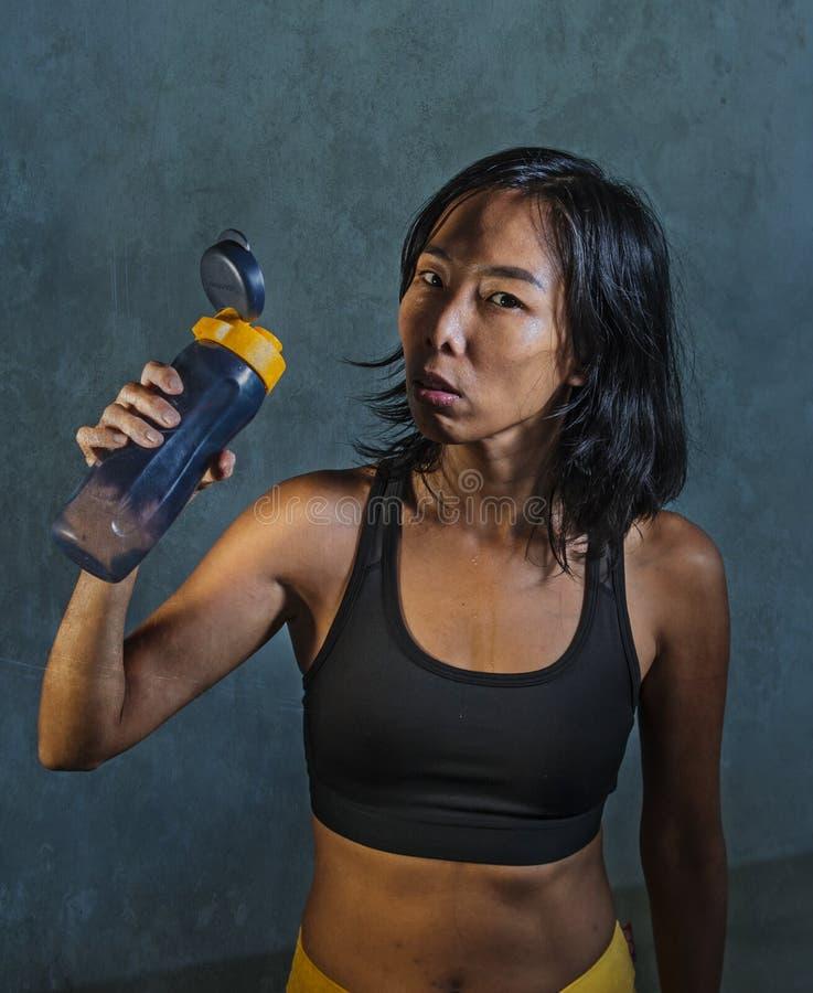 Retrato de la mujer coreana asiática atlética y apta joven en la presentación de consumición superior de la botella de agua de la imagen de archivo libre de regalías