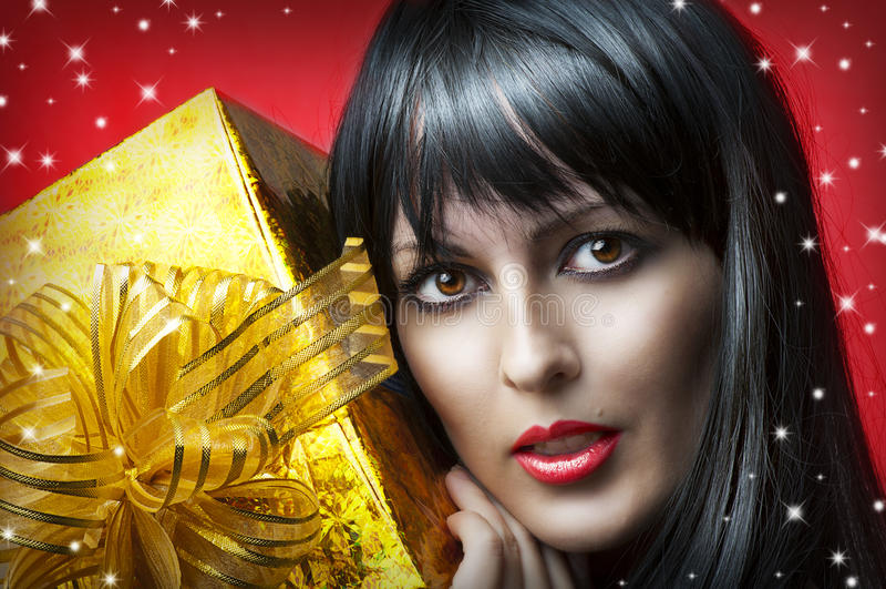 Retrato de la mujer de la belleza con el regalo de la Navidad del oro fotografía de archivo