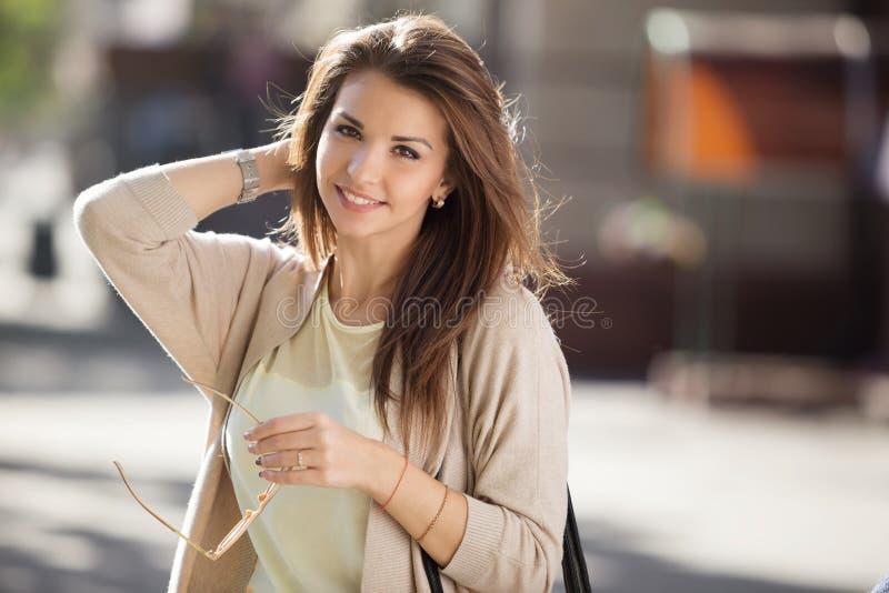 Retrato de la mujer de la belleza con sonrisa perfecta que camina en la calle y que mira la cámara imagenes de archivo