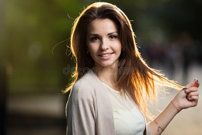Retrato de la mujer de la belleza con sonrisa perfecta que camina en la calle y que mira la cámara, luz de la puesta del sol imagenes de archivo