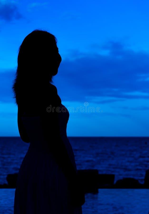 Retrato de la mujer de la silueta en fondo de la opinión del mar fotografía de archivo