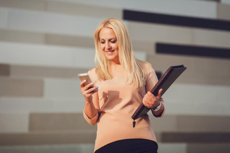 Retrato de la mujer de negocios al aire libre con el teléfono foto de archivo