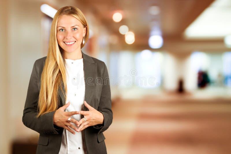 Retrato de la mujer de negocios hermosa que se coloca en oficina fotografía de archivo libre de regalías