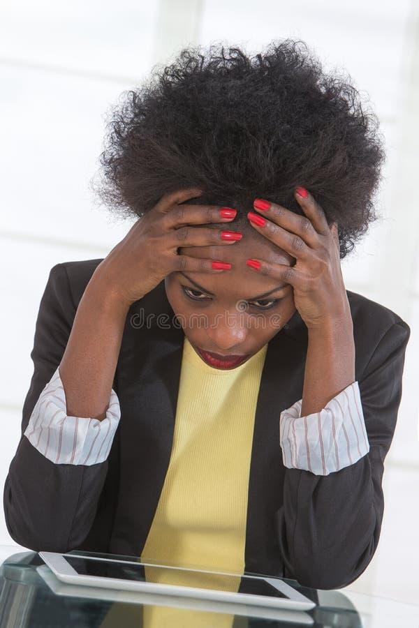 Retrato de la mujer de negocios infeliz negra madura en el escritorio en oficina imagen de archivo libre de regalías