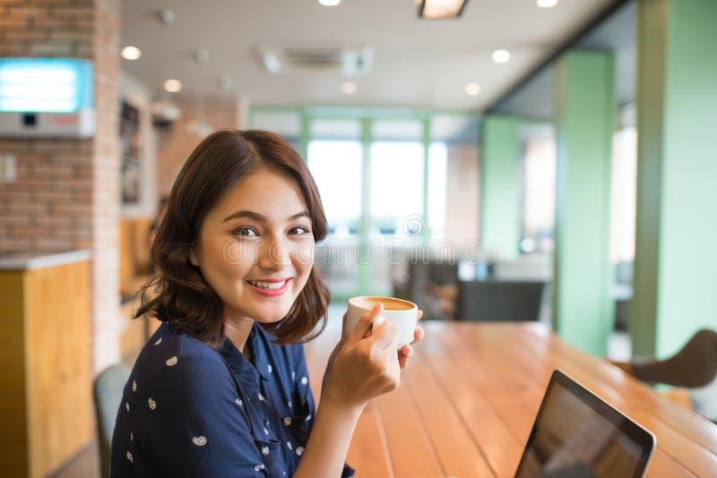 Retrato de la mujer de negocios joven feliz con la taza en drinkin de las manos fotografía de archivo libre de regalías