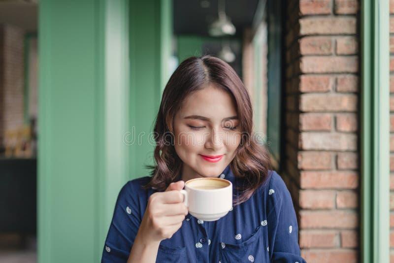 Retrato de la mujer de negocios joven feliz con la taza en drinkin de las manos foto de archivo