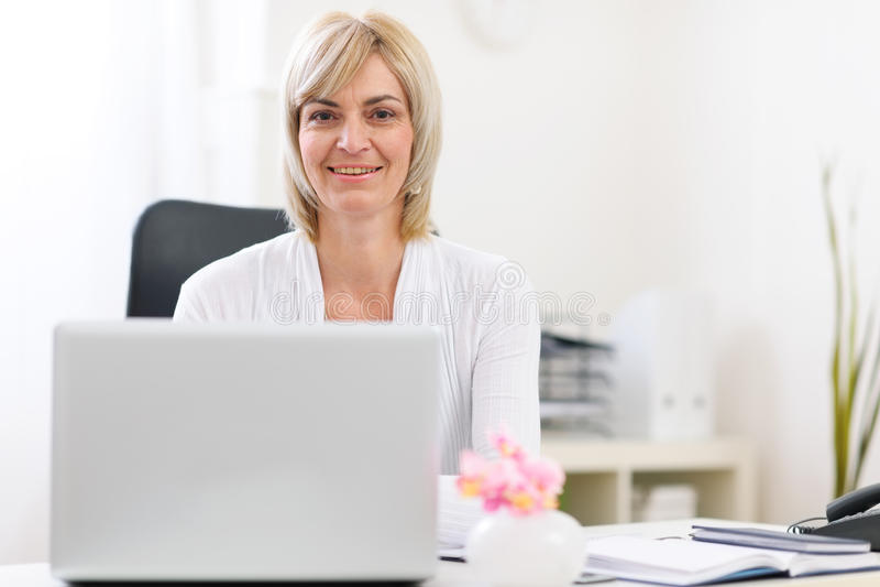 Retrato de la mujer de negocios mayor feliz en la oficina imagen de archivo libre de regalías