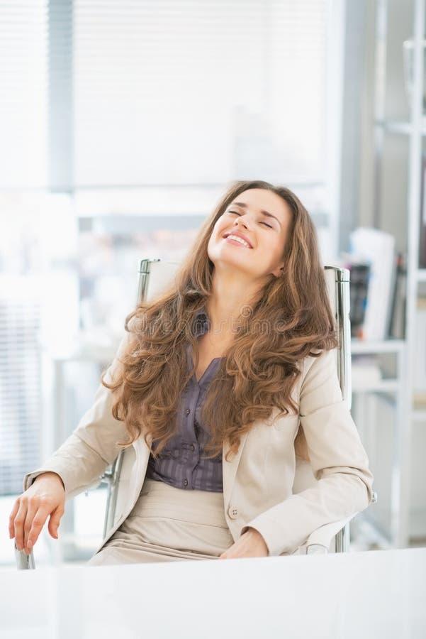 Retrato de la mujer de negocios que se sienta en oficina imagen de archivo