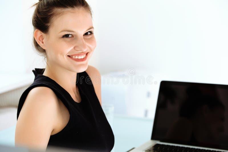 Retrato de la mujer de negocios sonriente con un ordenador portátil fotos de archivo