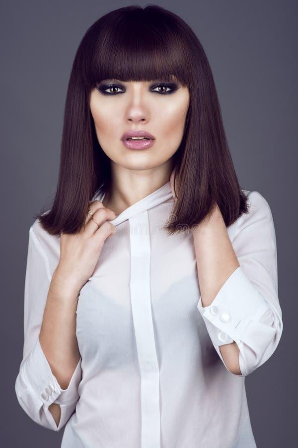 Retrato de la mujer de pelo oscuro joven magnífica que parece recta y que tira del cuello de su blusa con mirada cansada fotografía de archivo
