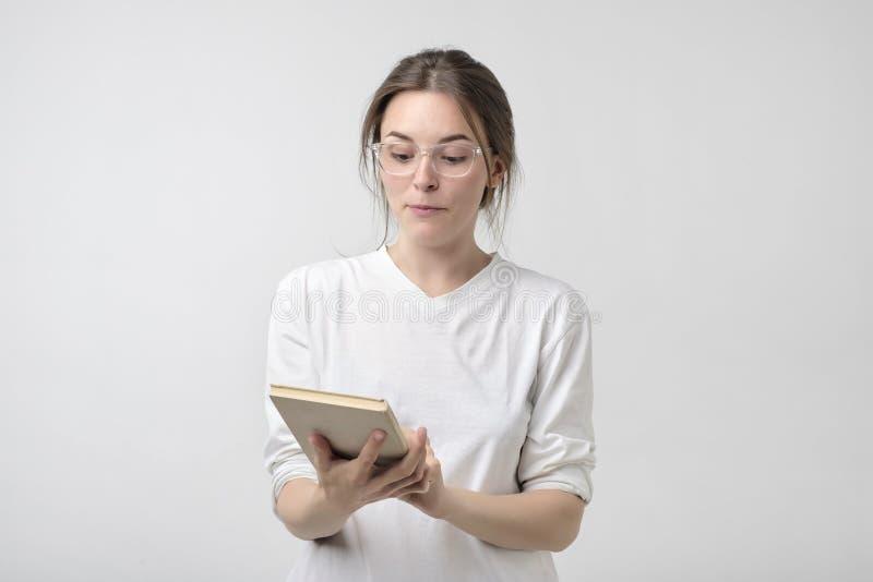 Retrato de la mujer del estudiante que lee un libro foto de archivo
