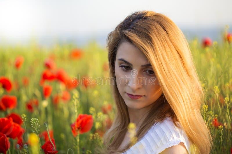 Retrato de la mujer del trastorno que se coloca en el campo de amapolas imagen de archivo