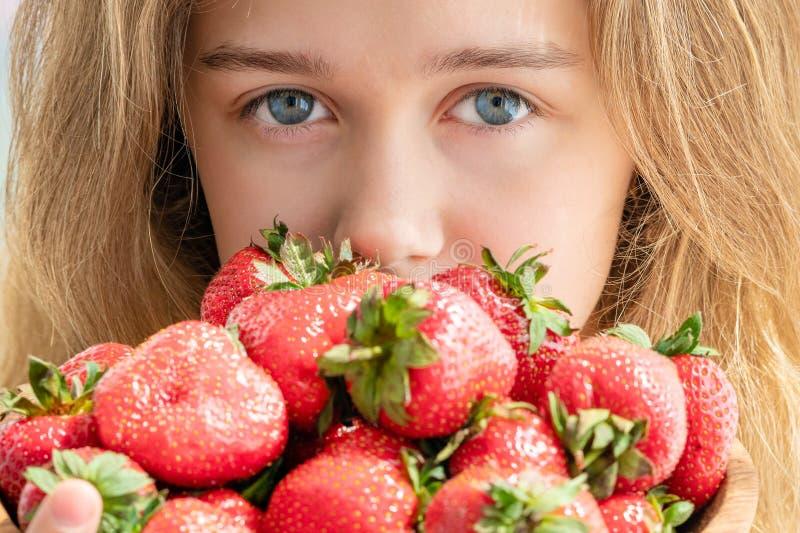 Retrato de la mujer del yaung que come las fresas Mujer sonriente feliz sana que come la fresa fotos de archivo