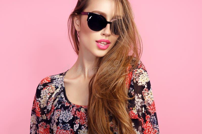 Retrato de la mujer delgada hermosa joven en vestido sexy con los labios sensuales en gafas de sol que llevan del estudio sonrisa imágenes de archivo libres de regalías