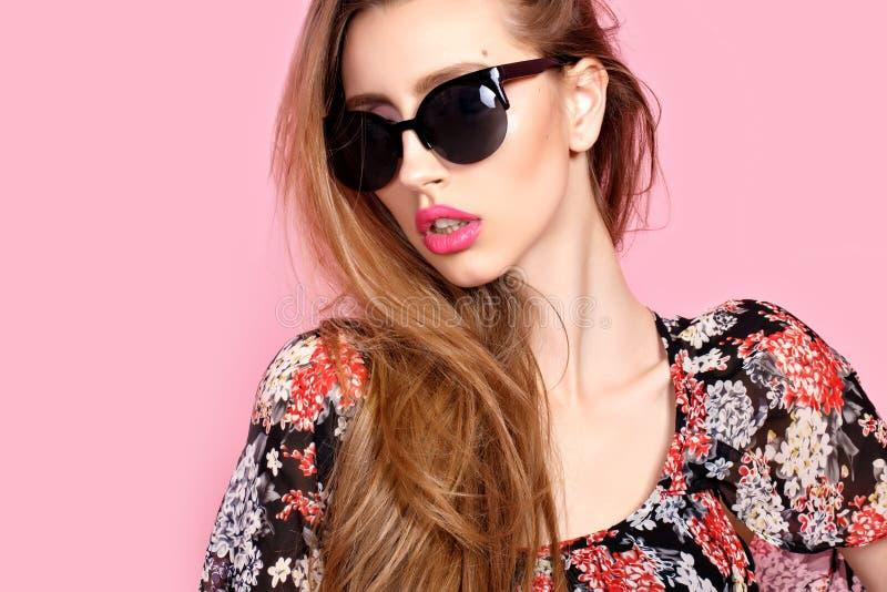 Retrato de la mujer delgada hermosa joven en vestido sexy con los labios sensuales en gafas de sol que llevan del estudio sonrisa fotografía de archivo