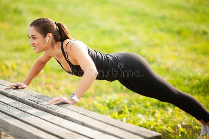 Retrato de la mujer deportiva hermosa 20s en la ropa de deportes que hace pectorales, y escuchando la música con auricular de bot imagen de archivo libre de regalías