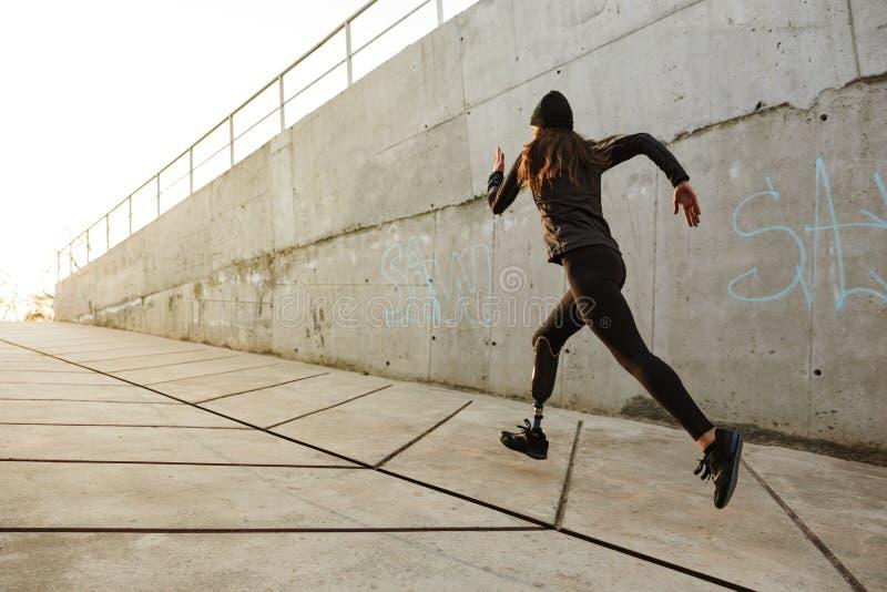 Retrato de la mujer discapacitada del atleta con la pierna prostética en pistas foto de archivo libre de regalías