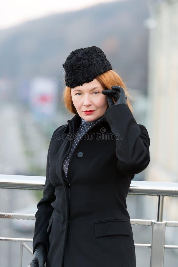 Retrato de la mujer diseñada en capa negra Señora roja del pelo en capa, sombrero y guantes Mirada seria del ` s de la mujer en u fotos de archivo libres de regalías