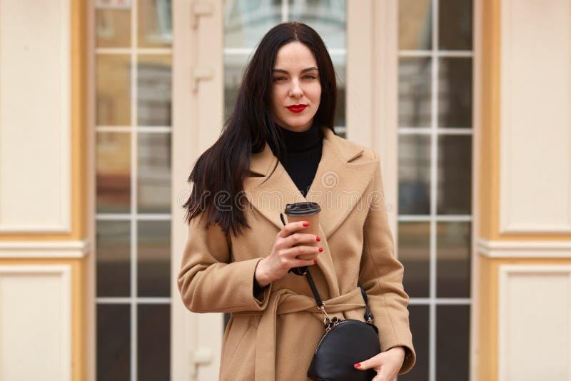 Retrato de la mujer elegante atractiva que lleva la capa beige y que bebe el café para llevar mientras que camina a través de la  fotos de archivo libres de regalías