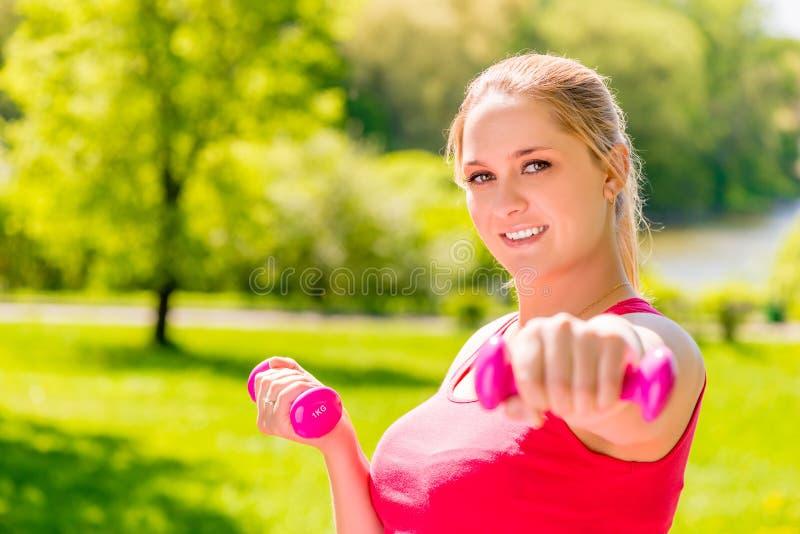 Retrato de la mujer embarazada activa feliz con pesas de gimnasia fotografía de archivo