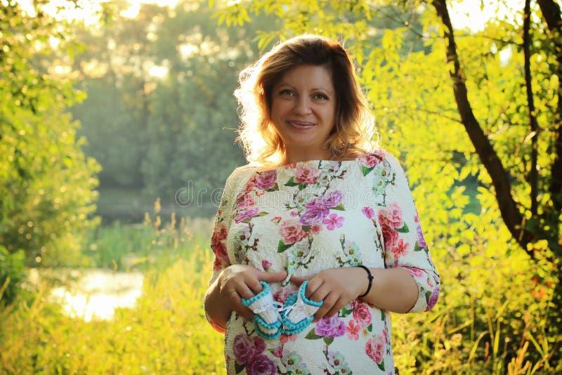 Retrato de la mujer embarazada hermosa joven Ella se sostiene en sus pequeños botines del bebé de las manos foto de archivo